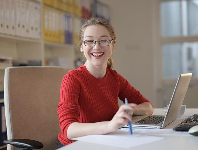 Girl at computer smiling at us