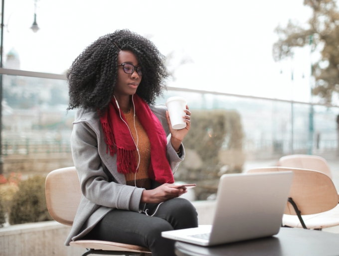 woman with headphones drinking coffee