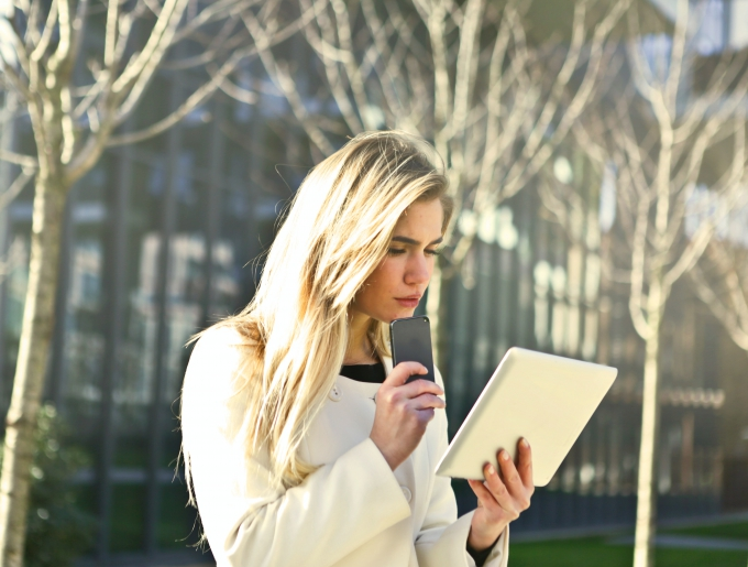 woman using phone and tablet